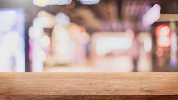 Piano d'appoggio di legno vuoto e fondo vago dell'interno del ristorante e della caffetteria