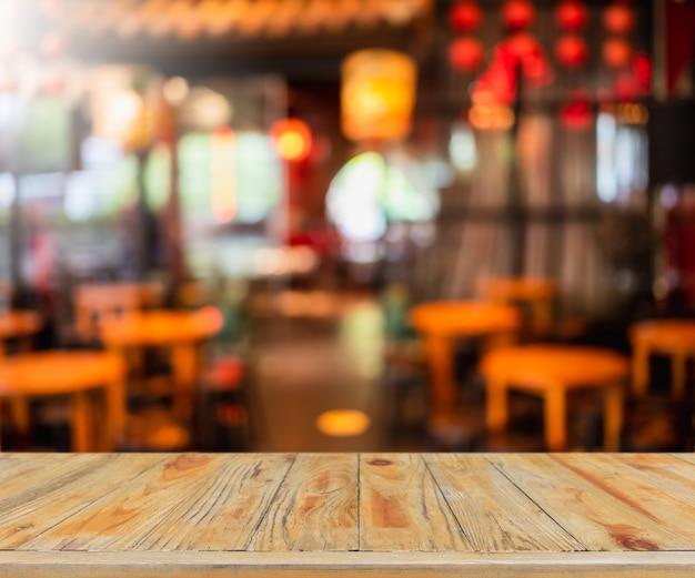 Piano d'appoggio in legno vuoto e interni sfocati della caffetteria e del ristorante