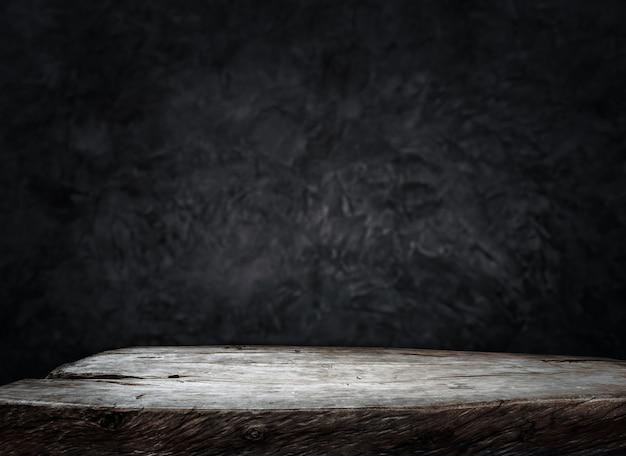 Bancone da tavolo in legno vuoto sul fondo scuro della parete