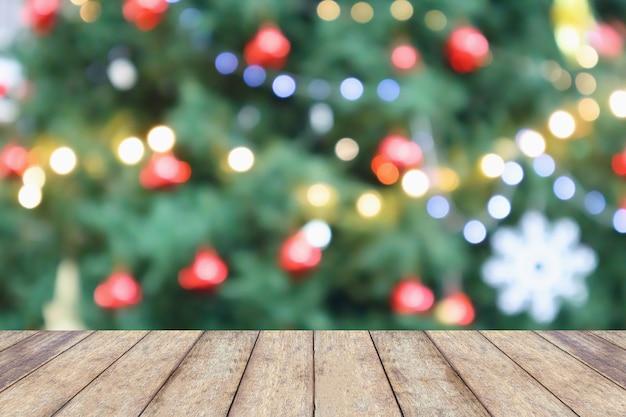 Svuoti il piano d'appoggio di legno con l'albero di natale astratto della sfuocatura con il fondo della luce del bokeh della decorazione per l'esposizione del prodotto