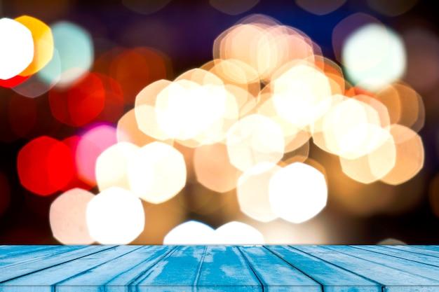 Vuoto del piano del tavolo in legno con astratto sfocato multicolore, rosa, rosso, bianco, giallo, blu, macchiato con bokeh sfocato luci dello sfondo della città