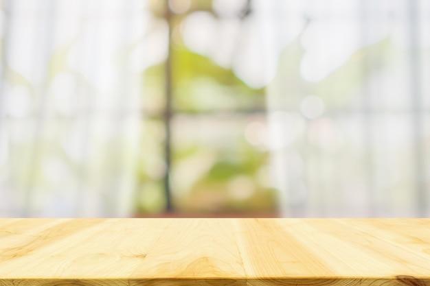 Piano del tavolo in legno vuoto con sfocatura finestra tenda bianca e sfondo verde giardino per modello di visualizzazione del prodotto