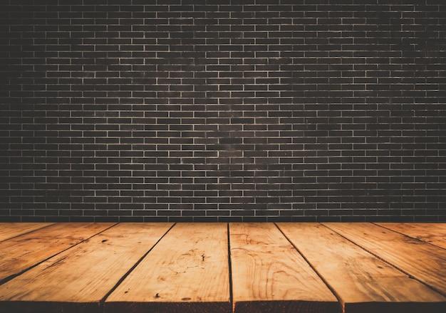 Piano tavolo in legno vuoto con sfondo muro di mattoni scuri.