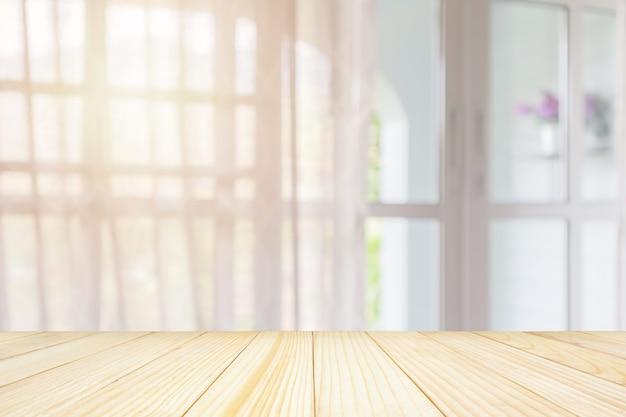 Svuoti il piano d'appoggio di legno con il fondo della sfuocatura astratta della tenda della finestra per l'esposizione del prodotto