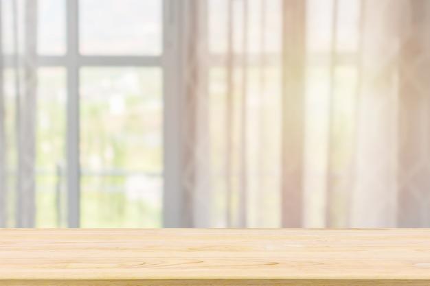 Svuoti il piano d'appoggio di legno con la priorità bassa della sfuocatura astratta della tenda della finestra per l'esposizione del prodotto