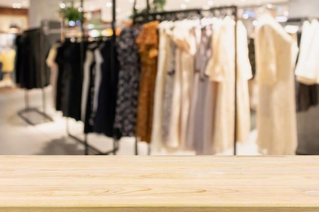 Tavolo in legno vuoto con vetrina del negozio di abbigliamento boutique alla moda donna nel centro commerciale