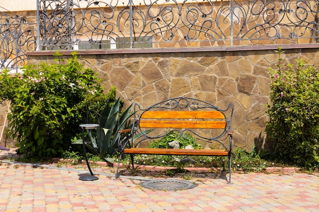 Panca di legno vuota con un posacenere in una soleggiata giornata estiva con un cactus sullo sfondo di un muro di pietra. stile mediterraneo.
