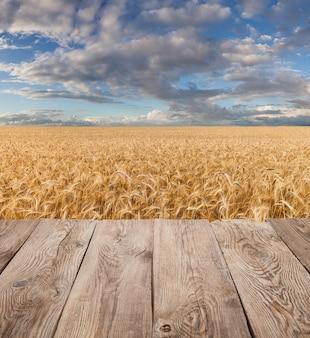 Tavolo vuoto ponte di legno sul campo di grano.