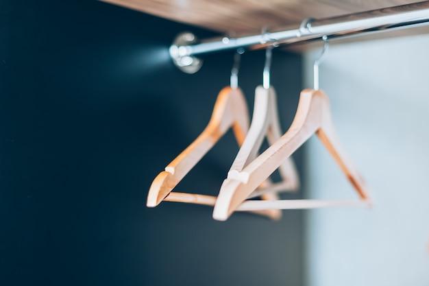 Grucce di legno vuote su rotaia nell'armadio. composizione di stile di vita con luce naturale e spazio di copia
