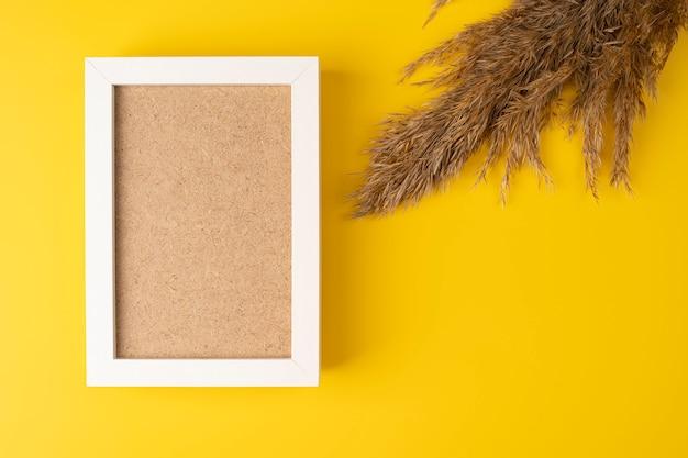Una cornice per foto in legno vuota giace su uno sfondo giallo, rami soffici, fiori secchi