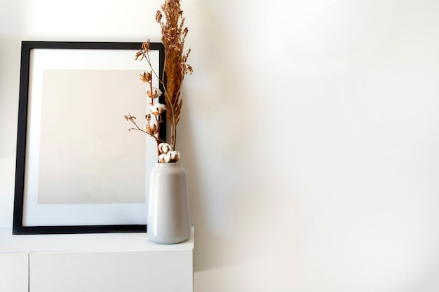 Modello vuoto della cornice di legno della foto con il vaso bianco e la pianta alla moda vicino alla parete bianca sulla tavola c