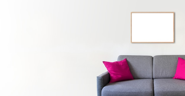 Cornice in legno vuota su un muro bianco sopra un divano. sfondo interno minimalista. banner orizzontale