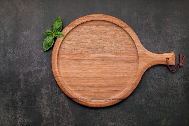 Piatto vuoto per pizza in legno allestito su cemento scuro. vassoio per pizza su fondo di cemento scuro disteso piatto e spazio di copia.