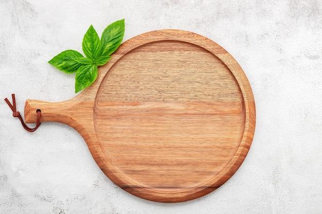 Piatto per pizza in legno vuoto impostato su cemento bianco. vassoio per pizza su fondo di cemento bianco laici piatta e spazio di copia.