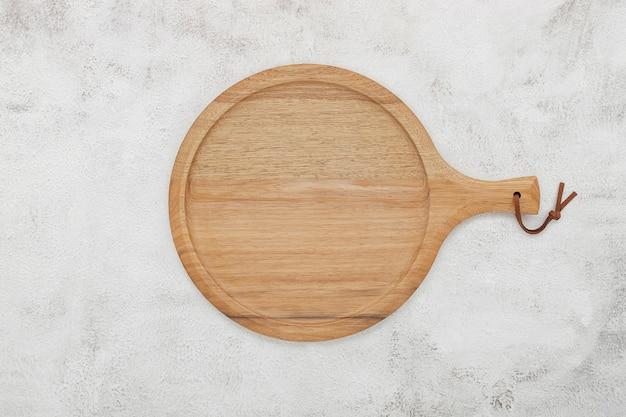 Piatto per pizza in legno vuoto impostato su cemento bianco. vassoio per pizza su fondo di cemento bianco piatto laici e spazio di copia.
