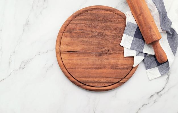 Piatto vuoto per pizza in legno con tovagliolo e mattarello impostato su tavolo da cucina in pietra di marmo. tagliere e tovaglia per pizza su fondo in marmo bianco.