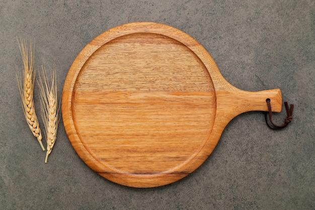 Piatto vuoto per pizza in legno con spighe di grano su fondo di cemento scuro.