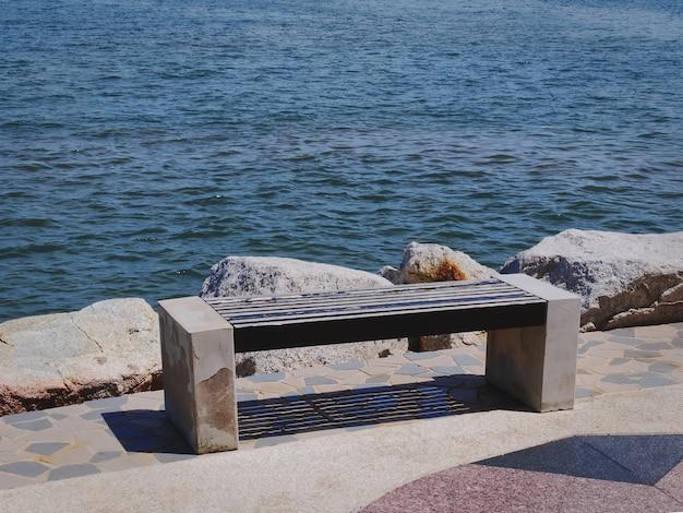 Panchina in legno vuota in riva al mare
