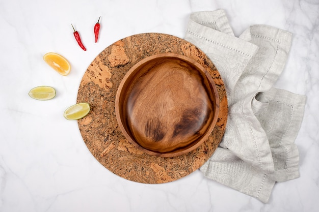 Piatto di legno vuoto su un tovagliolo e un sottopentola di sughero riscaldare con limone e pepe.
