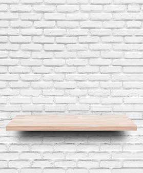 Mensola di legno vuota sul fondo del muro di mattoni bianchi.