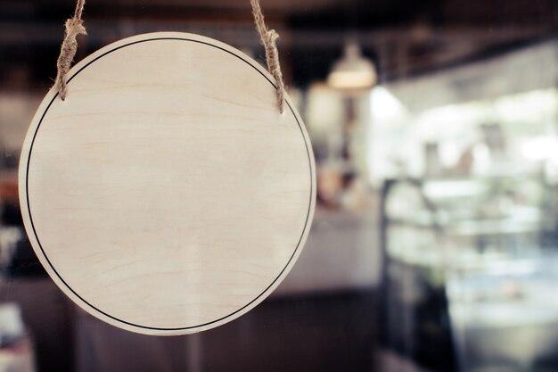 Cartello in legno vuoto appeso alla porta di vetro con luce solare nel moderno bar ristorante, spazio copia per pubblicità di testo, ristorante bar, marketing pubblicitario e concetto di piccolo imprenditore