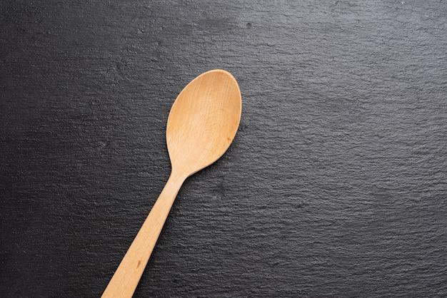 Cucchiaio di legno vuoto su una superficie nera, vista dall'alto
