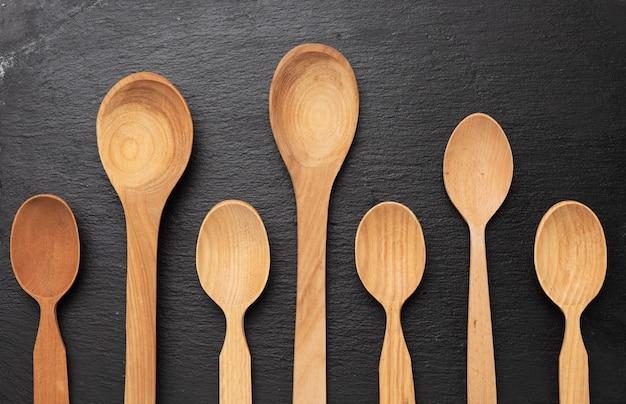 Cucchiai di legno vuoti su uno sfondo nero, vista dall'alto, impostare