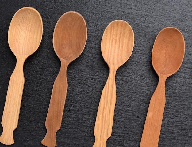Cucchiai di legno vuoti su uno sfondo nero, vista dall'alto