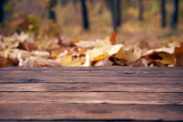 Tavolo in legno vuoto autunno foglie d'acero natura bokeh sfondo con un tema all'aperto paese, modello mock up per la visualizzazione del prodotto spazio copia