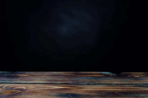 Tavolo in legno vuoto e parete nera per l'esposizione del prodotto con spazio per testo o foto.