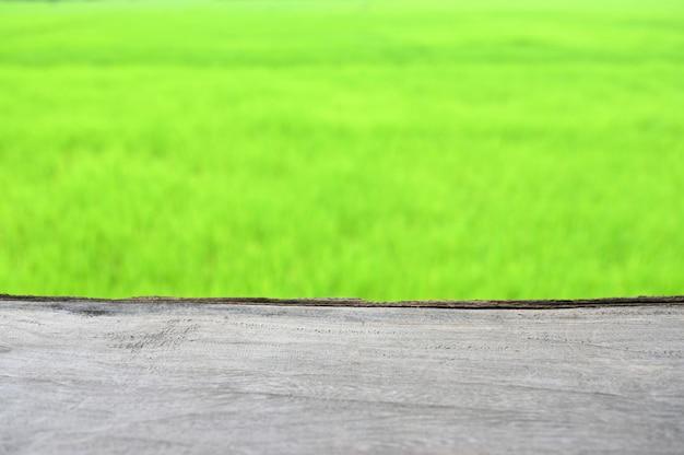 Svuoti la tavola di legno e il fondo verde vago delle risaie, pronto per il montaggio del prodotto