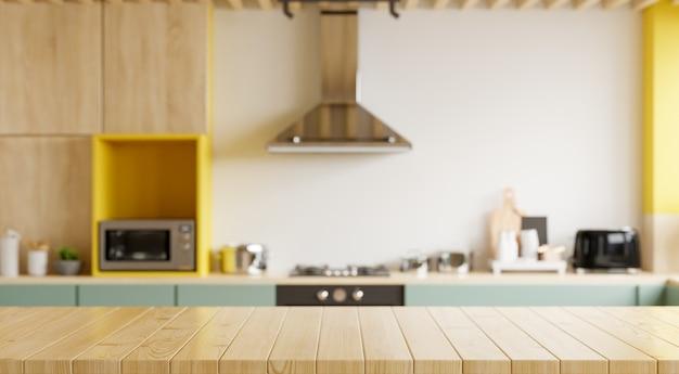 Tavolo in legno vuoto e cucina offuscata sfondo giallo muro