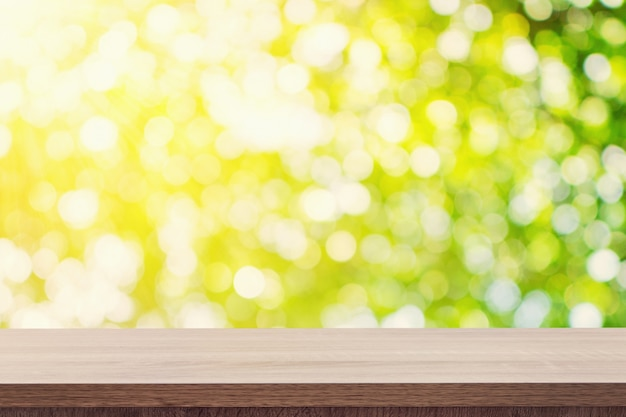 Tavolo in legno vuoto per il posizionamento o montaggio del prodotto e sfondo sfocato verde chiuso.