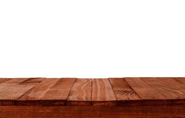 Tavolo vuoto in legno in un giardino estivo inondato di sole per il posizionamento o il montaggio di prodotti con particolare attenzione al piano del tavolo in primo piano, con sfondo bianco.