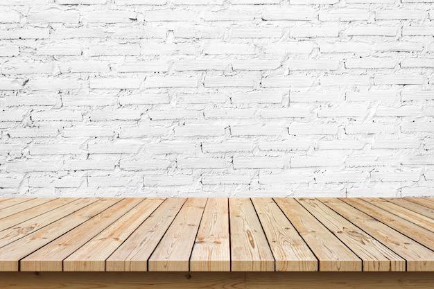 Piano del tavolo in legno vuoto su sfondo bianco muro di mattoni, utilizzato per visualizzare o montare i tuoi prodotti