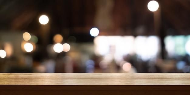 Svuoti il piano d'appoggio di legno con il fondo interno della caffetteria o del ristorante della sfuocatura, insegna panoramica. lo sfondo astratto può essere utilizzato per visualizzare o montare i tuoi prodotti.