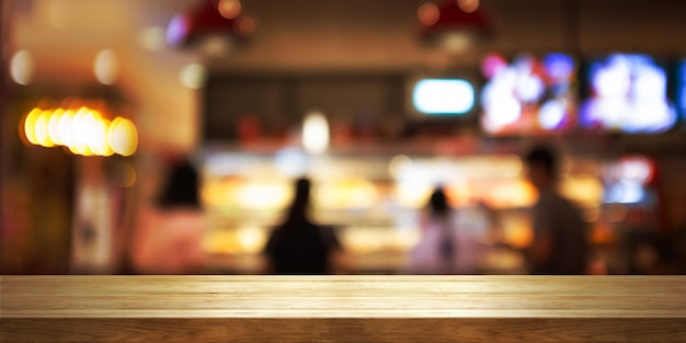 Svuoti il piano d'appoggio di legno con la caffetteria della sfuocatura o il fondo interno del ristorante.