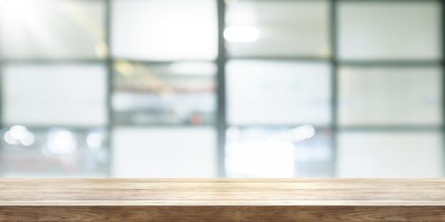 Svuoti il piano d'appoggio di legno con il fondo della finestra di coffeeshop della sfuocatura, insegna panoramica.