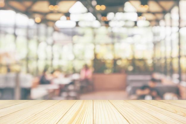Svuoti il piano d'appoggio di legno con la sfuocatura astratta interna della caffetteria del ristorante del caffè defocused con il fondo della luce del bokeh per l'esposizione del prodotto del montaggio