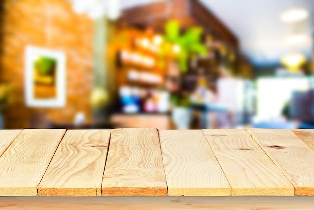 Piano del tavolo in legno vuoto con sfocatura della caffetteria con sfondo bokeh espositore del prodotto