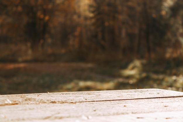 Un tavolo di legno vuoto e una foresta autunnale sfocata sullo sfondo. ottimo per il montaggio del display del prodotto.