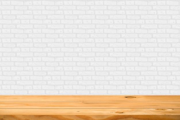 Svuoti la tavola di legno sopra il fondo bianco del mattone. pronto per il montaggio del display del prodotto.