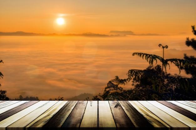 Tavola di legno vuota con nebbia di mare offuscata e sfondo di montagna. modello di visualizzazione del prodotto Foto Premium