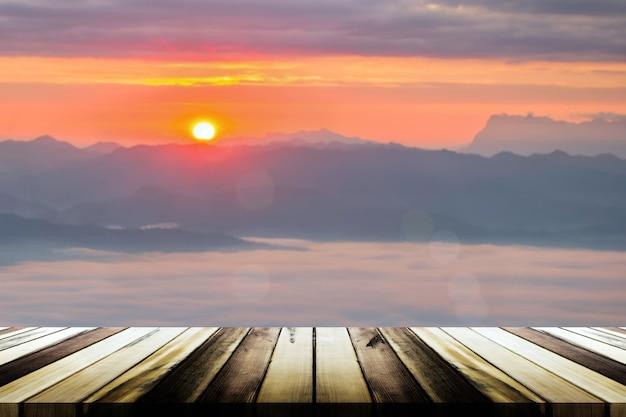 Tavola di legno vuota con nebbia di mare offuscata e sfondo di montagna. modello di visualizzazione del prodotto
