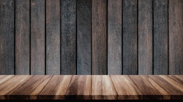 Tavola di legno vuota con il vecchio muro di legno