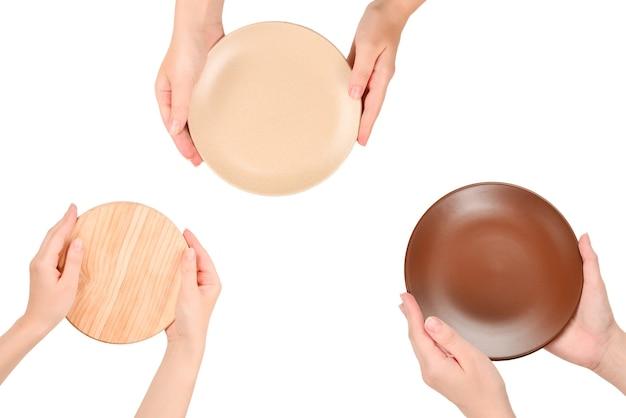 Vassoio di legno vuoto nelle mani della donna isolato su priorità bassa bianca.