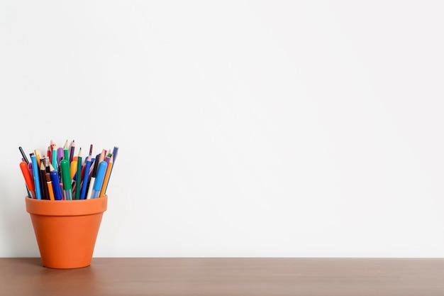 Scrivania vuota in home office con muro bianco e matite e cancelleria sul tavolo di legno