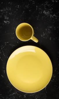 Piatto giallo vuoto e tazza di tè su fondo strutturato nero. vista dall'alto