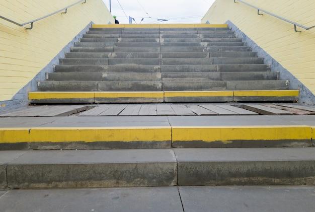 Passaggio pedonale sotterraneo giallo vuoto. tunnel e luce del giorno alla fine. passi verso l'alto all'attraversamento pedonale. un lungo tunnel di cemento con lanterne nella metropolitana della città.