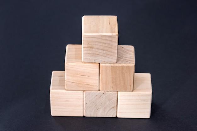 Cubi di legno gialli vuoti isolati sulla superficie nera